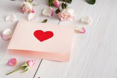 Pink rose flowers and handmade paper card with heart on white rustic wood. Valentine background with pink rose flowers and handmade paper card with heart on Royalty Free Stock Photos