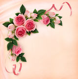 Pink rose flowers and ribbons corner arrangement on silk Royalty Free Stock Photo