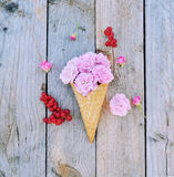 Pink rose flowers and ripe red currants in ice cream cone on rustic wooden background Royalty Free Stock Photos