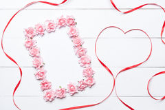 Pink rose frame with heart shaped red ribbon over white wooden b Royalty Free Stock Photos