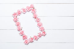 Pink rose frame over white wooden background. With empty copyspace Royalty Free Stock Images