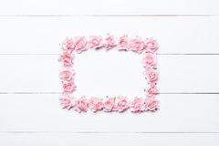 Pink rose frame over white wooden background Stock Photo