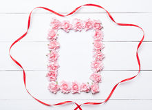 Pink rose frame with red ribbon over white wooden background Royalty Free Stock Photo