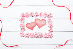 Pink rose frame with two hearts over white wooden table Royalty Free Stock Images