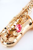 Pink Rose on a Gold Saxophone. A pink or red and white rose on a gold brass saxophone isolated against a high key white background in the vertical format Stock Photos
