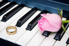 Pink rose and golden ring on the piano keyboard.  Stock Image