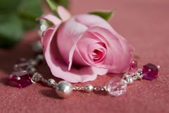 Pink rose and jewelery. Beautiful pink rose with vinous and silver color jewelery on it ISOLATED on red royalty free stock photography