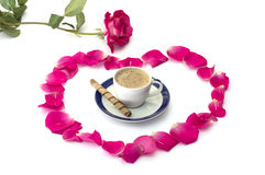 Pink rose lobes of roses and a cup of coffee at center Royalty Free Stock Photo