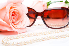 Pink rose, necklace and sunglasses Royalty Free Stock Images
