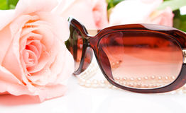 Pink rose, necklace and sunglasses Stock Photos