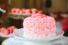 Pink Rose Ombré Wedding Cake. Pink roses ombré wedding cake on a vintage lace doily at a rustic vintage inspired wedding reception Royalty Free Stock Photos