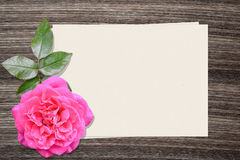 Pink rose and and paper on wood background Royalty Free Stock Photography