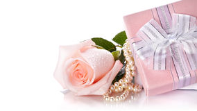 Pink rose and pearl beads and gift. Royalty Free Stock Images