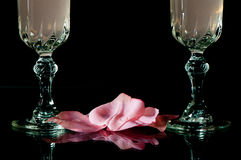 Pink Rose Petals and Wine. Pink rose petals and crystal wine glasses on black background Stock Photo