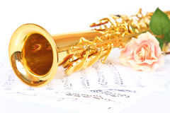 Pink rose, saxophone and music sheet. On a white background stock photos