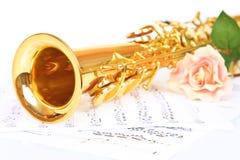 Pink rose, saxophone and music sheet Stock Photos