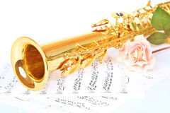 Pink rose, saxophone and music sheet. On a white background stock image