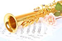 Pink rose, saxophone and music sheet Stock Image
