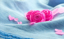 Pink rose and small hart on blue cloth background Royalty Free Stock Photography