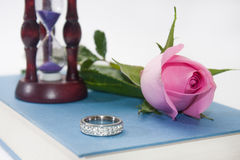 Pink rose with wedding ring and hourglass on the book Royalty Free Stock Image