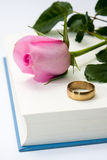 Pink rose and wedding ring on the opened book paper Royalty Free Stock Photo