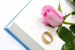 Pink rose and wedding ring on the opened book paper Royalty Free Stock Image