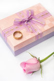 Pink rose and wedding ring on the pink gift box with bow Stock Photo