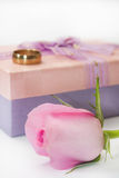 Pink rose and wedding ring on the pink gift box with bow Stock Image