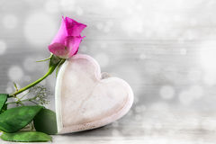 Pink rose and a wooden heart against a light gray bokeh backgrou Royalty Free Stock Images