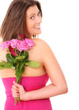 Pink roses. A picture of a young woman hiding a bunch of pink roses behind her back over white background Stock Photos