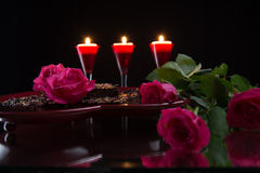 Pink roses and chocolate pastry on  a heart shaped tray. Candles Stock Photography