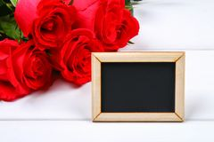 Pink roses with a blank chalkboard for text. Copy space for text. Template for March 8, Mother's Day, Valentine's Day. royalty free stock photography