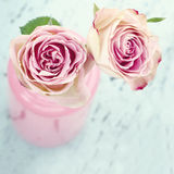 Pink roses in a bottle on wooden background Royalty Free Stock Photography