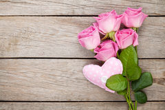 Pink roses bouquet and handmaded heart toy over wooden table Royalty Free Stock Photography