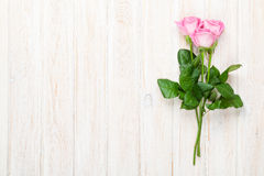 Pink roses bouquet over white wooden table Royalty Free Stock Images