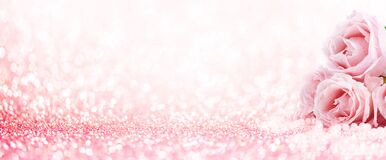 Pink roses bouquet and pearls on abstract blur pastel background. Wedding flowers and bright bokeh glitter backdrop
