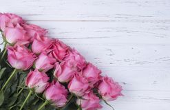 Pink roses bouquet on white wooden background with copy space. T. Pink roses bouquet on white wooden background. Top view Royalty Free Stock Photography
