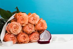 Pink roses and box holding wedding ring on blue background royalty free stock photos