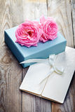 Pink roses with box and letter on wooden background in vintage s Stock Photo