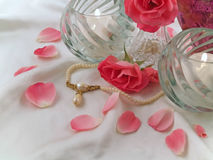Pink Roses, Candles, and Pearls. Still life of pink roses, lit candles and a pearl necklace of white satin Stock Image