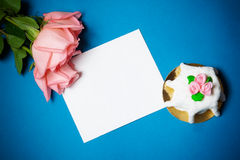 Pink roses, card  and cake with pink  marzipan roses on blue background Royalty Free Stock Photography
