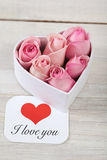 Pink roses with a card written saying love you Stock Photos