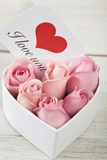 Pink roses with a card written saying love you Stock Photo