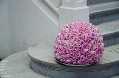 Pink roses centerpiece flower ball. Pink rose flower ball a large outdoor festive centerpiece standing by the stairs next to a white fence in the background A royalty free stock image