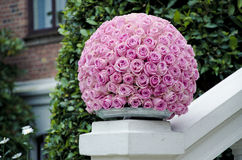 Pink roses centerpiece flower ball. Pink rose flower ball a large outdoor festive centerpiece standing on a white fence with a green bush and a brick wall stock photo