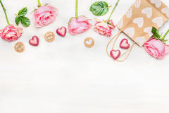 Pink roses with chocolate heart, shopping bag and round sign with message for you and with love on light background, top view. Royalty Free Stock Images