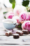 Pink roses, coffe and chocolate on the wooden table Royalty Free Stock Images
