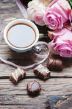 Pink roses, coffe and chocolate on the wooden table Royalty Free Stock Photography