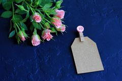 Pink roses on a dark background, decorative clothespin and paper with a space for text stock photos