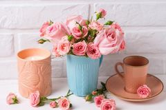 Pink roses flowers in blue cup, burning candle and little cup for coffee against white brick wall. royalty free stock images